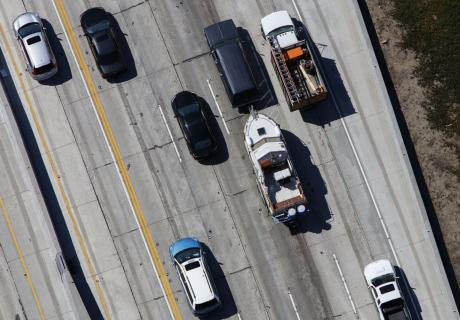 An SUV tows a boat on the freeway in Los Angeles, California.