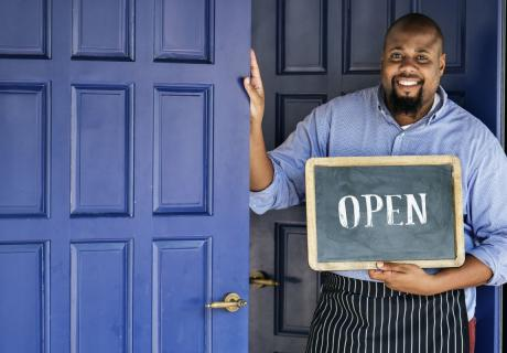 """African American small business owner in an apron holds a """"open"""" sign."""
