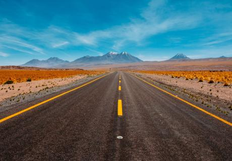 Highway in the desert with mountains and blue skies in the background.