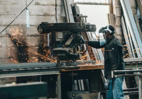 Sparks fly around a working operating a machine in a factory.