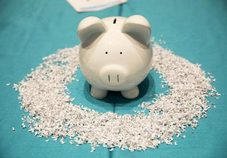 Piggy bank surrounded by shredded pieces of the U.S. tax code.