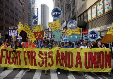 Protesters hold signs at a rally in support of minimum wage increase in New York City.