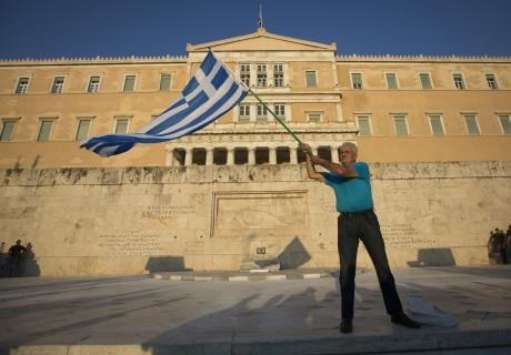 A man waves a Greek flag in Athens, Greece.