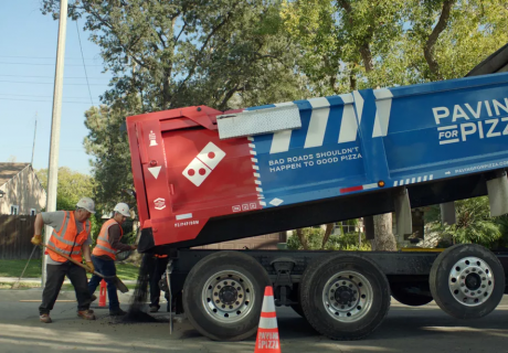 """A Domino's """"Paving for Pizza"""" work crew filling a pothole."""