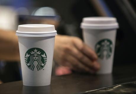 Coffee beverages sit on a counter inside a Starbucks.