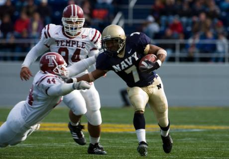 Navy running back, Reggie Campbell, stiff-arms Temple University players.