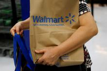 A customer carries a Walmart paper shopping bag during the grand opening of a Wal-Mart in Los Angeles, California.