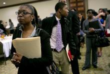 Yulanda Tappin, left, waits in a job recruitment line at a National Career Fairs job fair in Arlington, Virginia.