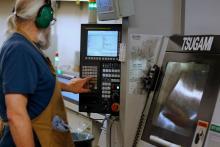 Factory worker running a machine.