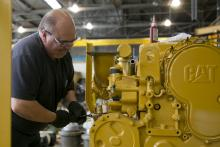 A worker works on a Caterpillar engine at the Ellicott Dredges factory in Baltimore, Md.