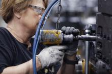A factory worker assembles components on a diesel engine at a Cummins plant in Seymour, IN.