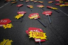 """Pro-union signs lay in the street before the start of a """"Fight for $15"""" rally in New York."""