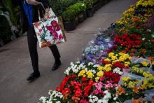 A pedestrian walks past plants displayed for sale in Manhattan's flower district in New York.