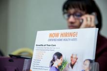 "A ""Now Hiring"" brochure for home health aides is displayed at a career fair in New York, NY."