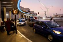 Travelers wait at a ride service pick up area at Los Angeles International Airport.