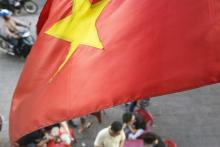 A Vietnamese national flag flies over the roadside in Ho Chi Minh City, Vietnam.