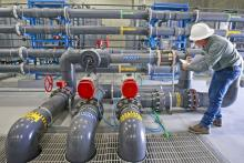 A worker takes water readings at a water treatment facility in West Valley City, UT.