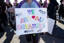 """An attendee holds a """"We Are All Dreamers"""" sign at an event in Las Vegas, NV."""