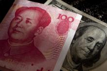 A one-hundred Chinese yuan note next to a one-hundred U.S. dollar note.