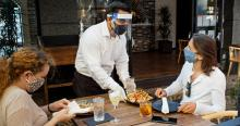Waiter Wearing PPE During Covid-19 Pandemic Serving Food to Diners Wearing Masks