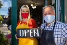 """A couple of small business owners hold and """"open"""" sign in front of their shop."""
