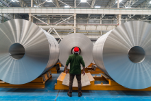 A worker stands between two large aluminum rolls.