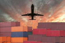Airplane flies over shipping containers.