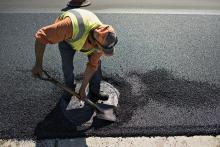 Construction worker repairs a pothole