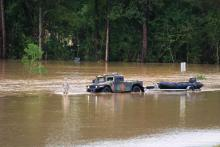 A Louisiana National Guardsman guides a Humvee through floodwaters off of I-12 outside of Denham Springs, LA.
