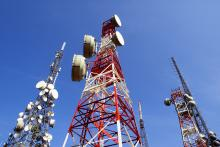 Cell phone towers in front of a clear, blue sky.