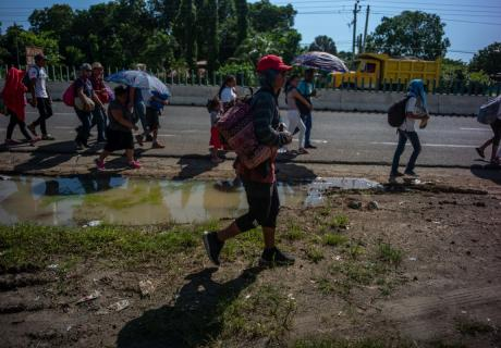 Central American refugees and asylum seekers walk along a road in Tapachula, Mexico.