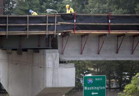 Contractors work on a highway ramp under construction in Alexandria, VA.
