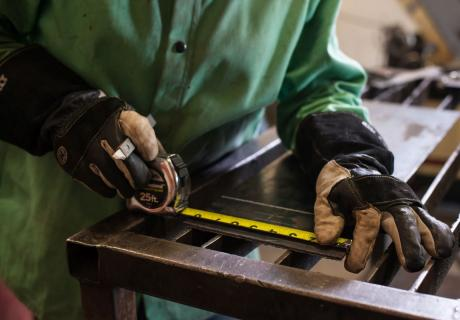 A student measures a piece of steel during a welding class at the Penn Commercial Business/Technical School in Washington, PA.