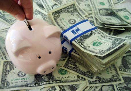 Piggy bank on a pile of dollar bills.