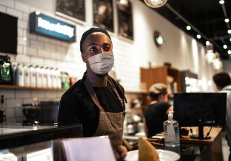 Barista standing at the counter of a coffee shop.