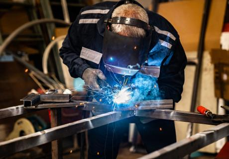 Senior man welding at workshop. He is dressed in full protective suit and gear.