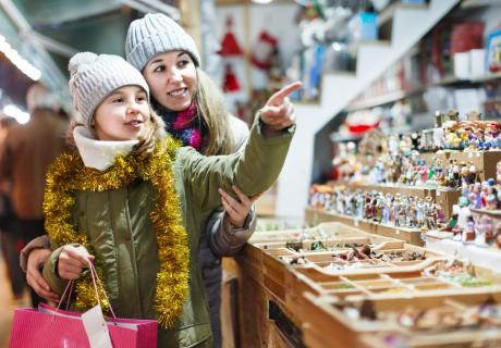 Smiling girl with woman are preparing for a Christmas and choosing a gifts for a their family.