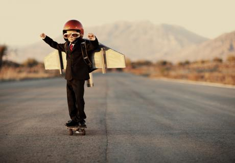 Boy standing on highway, wearing a helmet and airplane wings.