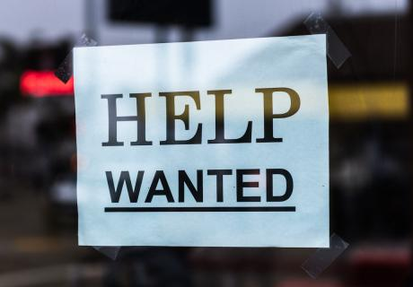 Help Wanted sign in a store window.