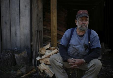 Retired coal miner Jimmy Smith takes a break while chopping firewood in Totz, Kentucky.
