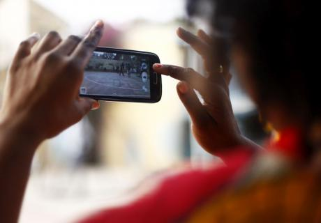 A woman uses her smartphone to record a basketball game in Dakar, Senegal.