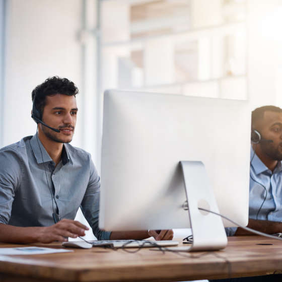 two male coworkers with headsets on laptops