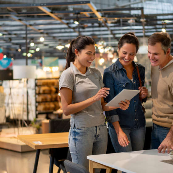Three smiling people stand in a hardware/home improvement store. The woman on the left holds a tablet, which the man and woman on the right examine..