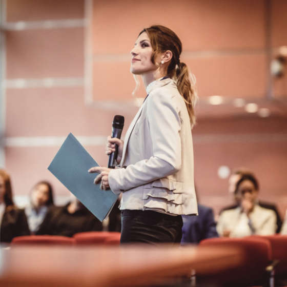 woman speaking in front of audience