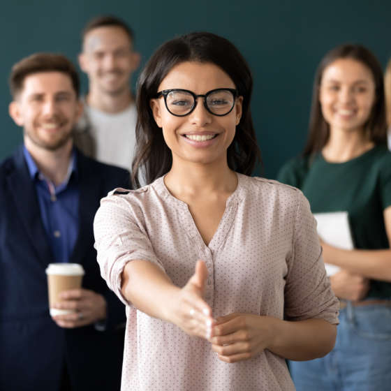 woman at the forefront of a group of people with a hand out to shake hands for a job interview
