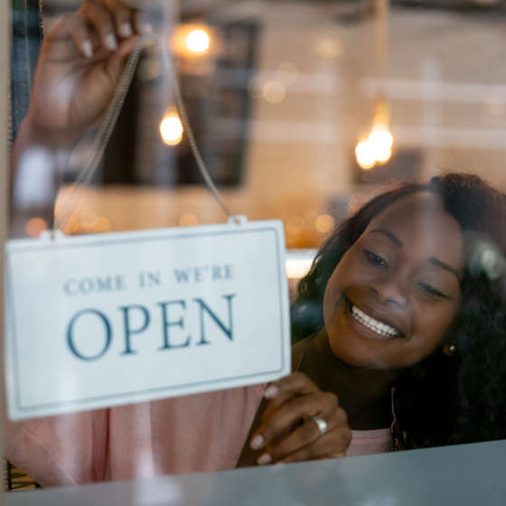 woman holding open sign in business window