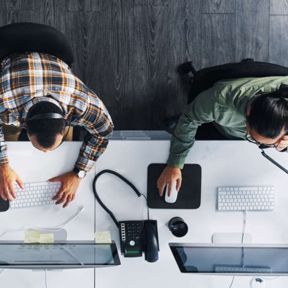 top view of two employees working on desktops