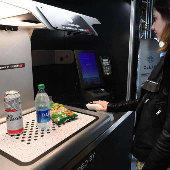 woman purchasing food and drink at clear kiosk in stadium