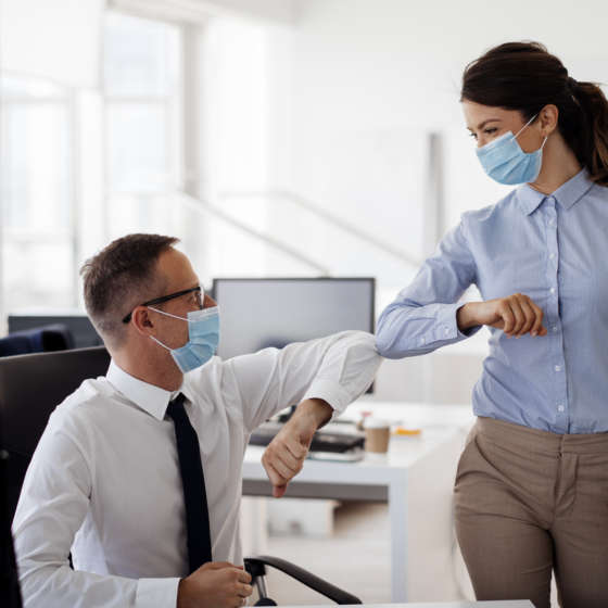 coworkers wearing masks bump elbows in office