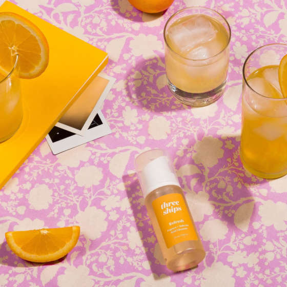 A bottle of Three Ships Refresh cleanser lays on its side next to a cocktail and pieces of fruit.